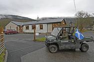 Un hombre acude a votar con una bandera escocesa, en Kinlochard.