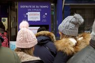 Decenas de personas hacen cola este domingo en la administración de Loterías Doña Manolita, en Madrid, para comprar la tradicional lotería de Navidad.