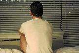 Un paciente sentado de espaldas en la cama de un hospital para ocultar su rostro.