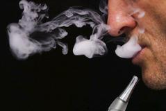 Un hombre fuma un cigarrillo electrónico.