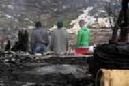 Tres inmigrantes observan el campamento chabolista de Palos de la Frontera arrasado por las llamas.
