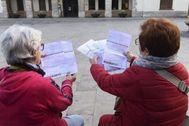 Dos vecinas de Barberà con documentos del tributo metropolitano.
