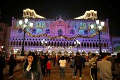 People enjoy a light show on the building of Venetian <HIT>Macao</HIT> casino in Macau