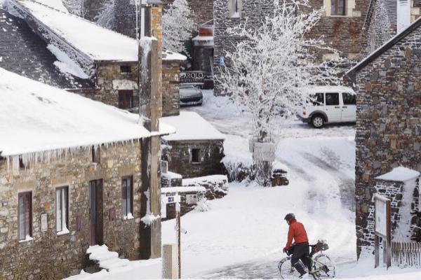Un hombre pasea en bicicleta por un nevadísimo O Cebreiro, en Lugo.
