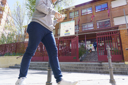 Un chico camina con un móvil frente a un colegio.