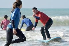 Uno de los chicos que participa en la terapia surfea ante la mirada de la monitora de la Asociación Solo Surf.