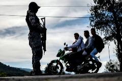 Tres personas en motocicleta atraviesan un control en Cheran, estado de Michoacán, vigilado por militares.