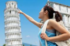 Una turista haciéndose una foto simulando que inclina la torre.