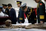 Militares chinos observan los restos de soldados.