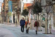 Varios vecinos pasean por la reformada calle de San Pedro en El Cabanyal.