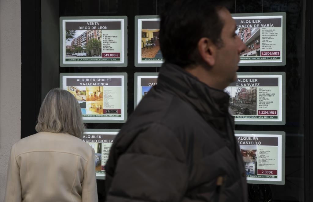Dos personas ante un escaparate con anuncios 'físicos' de venta de inmuebles en Madrid.
