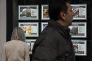 Dos personas pasan ante el escaparate de una oficina inmobiliaria, en Madrid.