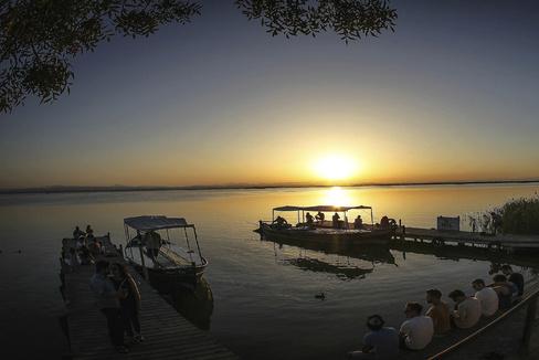 Un grupo de personas observan el atardecer desde uno de los embarcaderos del lago de l'Albufera en Valencia.
