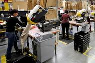 Empleados de Amazon empaquetan compras en una planta del grupo en España.