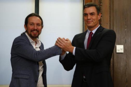 Pablo Iglesias y Pedro Sánchez se dan la mano tras la firma del pacto...
