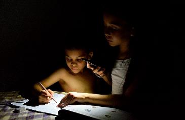 Dos niños estudian a la luz de un móvil en Maracaibo.
