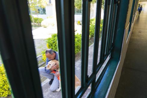 Emilio, preso desde hace más de una década, abraza a Rey, unos de los perros terapeutas de la cárcel de Valdemoro.