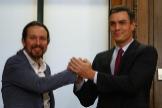Pablo Iglesias y Pedro Sánchez se dan la mano tras firmar su pacto de Gobierno.