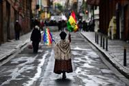 Una votante de Evo Morales pasea por La Paz con la bandera del país y la Wiphala.