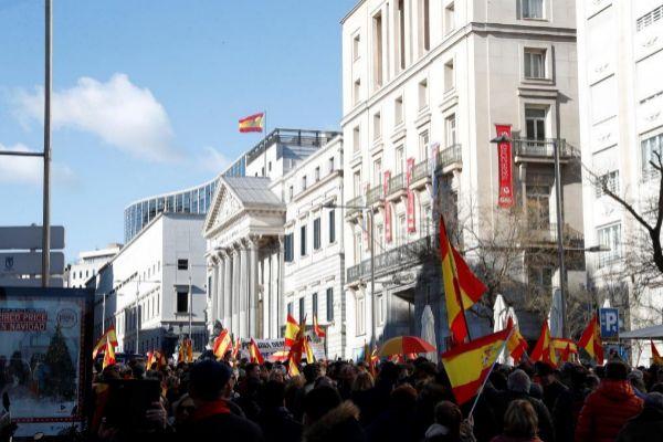 Manifestantes congregados en la Carrera de San Jerónimo mientras en el Congreso de los Diputados se celebra el debate para investir a Pedro Sánchez como presidente.