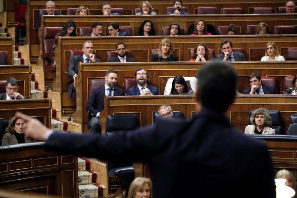 El presidente de Vox, Santiago Abascal, escucha al candidato a la...