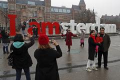 Turistas posan junto al cartel de Ámsterdam.