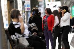 Varias mujeres conversan a través de sus teléfonos móviles en la calle.