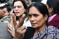 La madre de la joven violada hace un signo de victoria a la salida del tribunal, en Nueva Delhi.