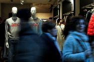 Varias persona pasan ante el escaparate de una tienda en Valencia en el primer día de rebajas.