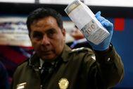 Un policía sostiene el dinero confiscado en el aeropuerto de La Paz.