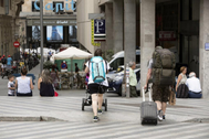 Varios turistas con sus maletas en el centro de Madrid.