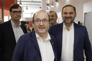 Salvador Illa (izqda.), detrás del presidente del PSC, Miquel Iceta, y junto a José Luis Ábalos, en un acto en Barcelona.