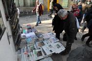 Iraníes leen las portadas con el reconocimiento del error humano.
