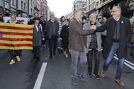 El diputado de Podemos Roberto Uriarte saluda a Eduard Pujol (JxCat,) en presencia de Josetxo Arrieta, este sábado, en una manifestación, en Bilbao.