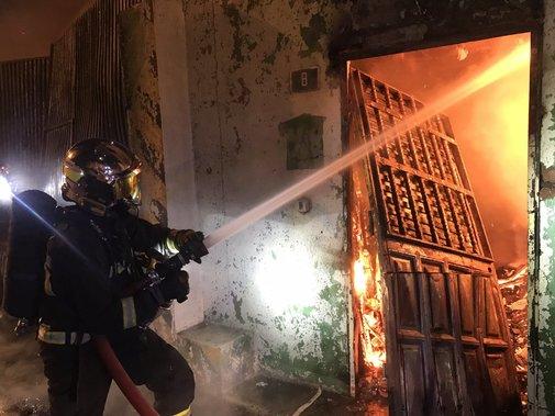 Bomberos trabajan en la extinción del fuego declarado en una...