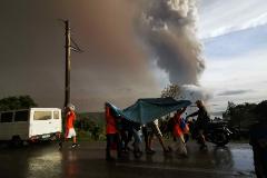 Varias personas se refugian de la ceniza bajo una manta de plástico en Tagaytay (Filipinas).