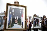 Una activista climática protesta con un retrato boca abajo de Macron.