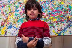 """El artista alemán Mikail Akar, de 7 años de edad, posa delante de una edición limitada de su pintura """"Champi"""", antes de la inauguración de su exposición """"Manus 11"""" en Berlín."""