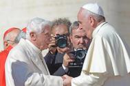 El Papa Francisco y el Papa emérito Benedicto XVI se saludan en una foto de archivo de 2014.