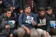 Estudiantes iraníes sostienen fotos de las víctimas del avión.