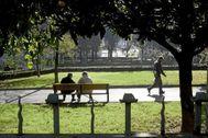 Dos hombres descansan en un banco del parque Dos Hermanos de Barakaldo.