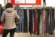 Una mujer mira la ropa de unos grandes almacenes durante las últimas rebajas.