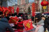 Varias personas compran en un mercado callejero de Pekín.