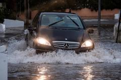 Un coche transita una calle inundada de Cala de Bou (Ibiza).