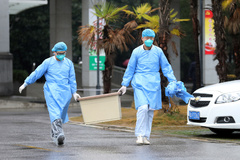 Medical staff carry a box as they walk at the Jinyintan hospital, where the patients with pneumonia caused by the new strain of coronavirus are being treated, in <HIT>Wuhan</HIT>