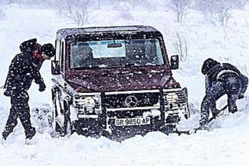 Dos hombres intentan sacar su todo terreno atrapado en la nieve cerca de Yecla, Murcia.