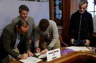 El alcalde Santano, en el centro, observa la firma entre el teniente alcalde y el edil de Podemos.