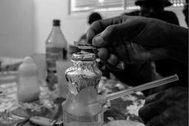Un hombre preparando una dosis de heroína.