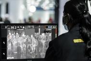Una oficial revisa una cola de pasajeros en el aeropuerto de Kuala Lumpur.