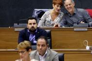 Los parlamentarios de Bildu Bakartxo Ruiz y Adolfo Araiz (arriba) observan a María Chivite (abajo) durante el pleno de investidura.